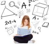 Κορίτσι σπουδαστών που μελετά και που διαβάζει το βιβλίο Στοκ Εικόνα