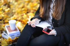 Κορίτσι σπουδαστών που χρησιμοποιεί το κινητό τηλέφωνό της κατά τη διάρκεια της μελέτης Στοκ Εικόνες