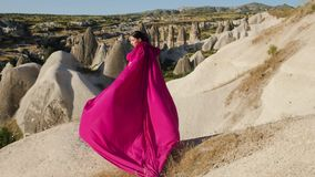 Κορίτσι στάσεις στις μακριές πορφυρές φορεμάτων υψηλές σε έναν βράχο σε Cappadocia απόθεμα βίντεο