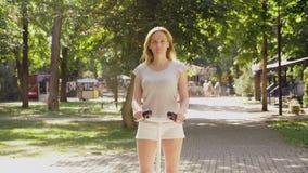 Κορίτσι στα άσπρα σορτς, που οδηγούν ένα Segway σε μια σαφή ηλιόλουστη ημέρα έντονο φως θερινών πάρκων και ήλιων 4k, σε αργή κίνη φιλμ μικρού μήκους