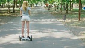 Κορίτσι στα άσπρα σορτς, που οδηγούν ένα Segway σε μια σαφή ηλιόλουστη ημέρα έντονο φως θερινών πάρκων και ήλιων 4k, σε αργή κίνη απόθεμα βίντεο
