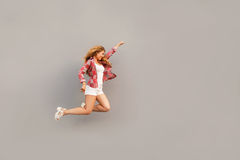 Κορίτσι στα άσπρα σορτς στον τοίχο υποβάθρου prigaet όπως τον υπεράνθρωπο Στοκ Εικόνες