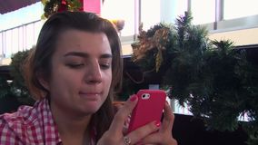 Κορίτσι στα έξυπνα ρολόγια που δακτυλογραφεί σε ένα smartphone στο φραγμό εστιατορίων φιλμ μικρού μήκους