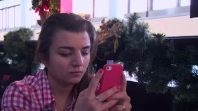 Κορίτσι στα έξυπνα ρολόγια που δακτυλογραφεί σε ένα smartphone στο φραγμό εστιατορίων απόθεμα βίντεο