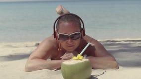 Κορίτσι στα ακουστικά που βρίσκονται στην παραλία και που προσέχουν την καρύδα απόθεμα βίντεο