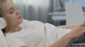 Κορίτσι στα ακουστικά που δακτυλογραφεί στο lap-top, που κουβεντιάζει με τους φίλους στο κοινωνικό δίκτυο φιλμ μικρού μήκους