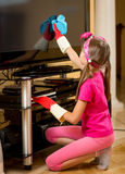 Κορίτσι στα λαστιχένια γάντια που καθαρίζουν την οθόνη TV από τη σκόνη με το ύφασμα Στοκ Φωτογραφία