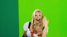 Κορίτσι στα βαυαρικά θέλγητρα κοστουμιών στο χέρι τους και την παρουσίαση του αντίχειρα πράσινη οθόνη απόθεμα βίντεο