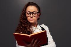 Κορίτσι στα γυαλιά που κρατά το βιβλίο και την ανάγνωση Στοκ Φωτογραφίες