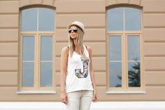 Κορίτσι στα γυαλιά ηλίου και καπέλο που στέκεται κοντά στο σπίτι Στοκ Εικόνες