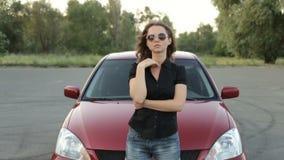Κορίτσι στα γυαλιά ηλίου που θέτουν στο κόκκινο κλίμα αυτοκινήτων απόθεμα βίντεο