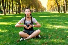 Κορίτσι στα γυαλιά ηλίου που κάθεται στη χλόη στο πάρκο και το υπόλοιπο Στοκ Εικόνες
