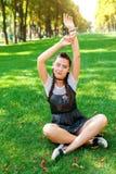 Κορίτσι στα γυαλιά ηλίου που κάθεται στη χλόη στο πάρκο και το υπόλοιπο Στοκ φωτογραφία με δικαίωμα ελεύθερης χρήσης