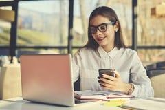 Κορίτσι στα γυαλιά που λειτουργούν τις αναφορές και τα φυλλάδια που λειτουργούν με τα apps που εγκαθίστανται στο φορητό προσωπικό Στοκ φωτογραφία με δικαίωμα ελεύθερης χρήσης