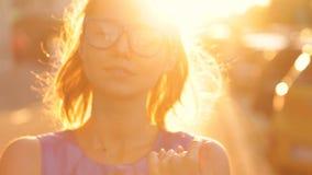 Κορίτσι στα γυαλιά στο υπόβαθρο του ηλιοβασιλέματος απόθεμα βίντεο