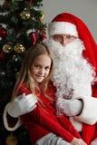Κορίτσι στα γόνατα Άγιου Βασίλη στοκ φωτογραφίες