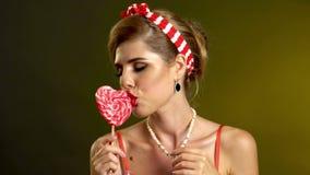 Κορίτσι στα καρφίτσα-επάνω ριγωτά lollipops γλειψίματος ύφους απόθεμα βίντεο