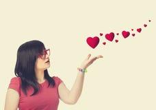Κορίτσι στα κόκκινα γυαλιά και τις αφηρημένες καρδιές στο άσπρο υπόβαθρο. Στοκ Φωτογραφία