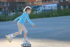 Κορίτσι στα μπλε σαλάχια κυλίνδρων στην παιδική χαρά Στοκ Εικόνες
