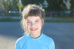 Κορίτσι στα μπλε χαμόγελα στην παιδική χαρά στη θερινή ηλιόλουστη ημέρα Στοκ φωτογραφία με δικαίωμα ελεύθερης χρήσης