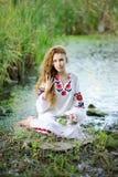 Κορίτσι στα ουκρανικά εθνικά ενδύματα με τα στεφάνια των λουλουδιών ο Στοκ φωτογραφία με δικαίωμα ελεύθερης χρήσης