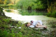 Κορίτσι στα ουκρανικά εθνικά ενδύματα με τα στεφάνια των λουλουδιών ο Στοκ Εικόνες