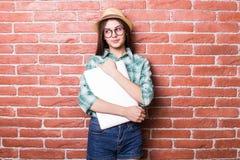 κορίτσι στα περιστασιακά ενδύματα, το καπέλο και eyeglasses που θέτουν, χαμογελώντας και με το στενό lap-top στα χέρια Στοκ Εικόνες