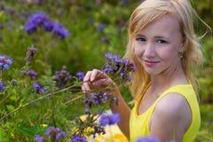 Κορίτσι στα πορφυρά λουλούδια υπαίθρια το καλοκαίρι Στοκ Φωτογραφίες