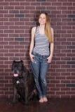 Κορίτσι στα τζιν και πουκάμισο που στέκεται αγκαλιάζοντας έναν μεγάλο κάλαμο Corso σκυλιών Στοκ Φωτογραφίες