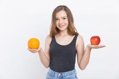 Κορίτσι στα τζιν που κρατούν πορτοκαλιά και το μήλο Στοκ φωτογραφία με δικαίωμα ελεύθερης χρήσης