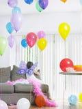 Κορίτσι στα φτερά νεράιδων με τα μπαλόνια στον καναπέ Στοκ Φωτογραφία