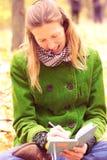 Κορίτσι στα φύλλα φθινοπώρου με ένα σημειωματάριο Στοκ Εικόνες
