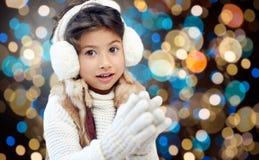 Κορίτσι στα χειμερινά καλύμματα αυτιών πέρα από τα φω'τα διακοπών Στοκ Φωτογραφία