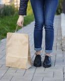 Κορίτσι στα όμορφα παπούτσια που κλίνονται πέρα από μια τσάντα εγγράφου Στοκ Φωτογραφία