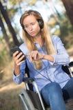 Κορίτσι στην αναπηρική καρέκλα που ακούει τη μουσική στη φύση Στοκ Εικόνα