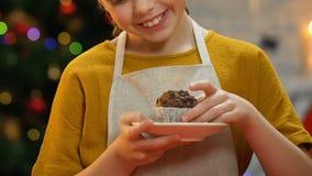 Κορίτσι στην εκμετάλλευση ποδιών cupcake, χαμογελώντας στη κάμερα, ευτυχής παιδική ηλικία Χριστουγέννων φιλμ μικρού μήκους