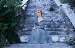 Κορίτσι στην εκλεκτής ποιότητας συνεδρίαση φορεμάτων στα σκαλοπάτια Στοκ εικόνα με δικαίωμα ελεύθερης χρήσης