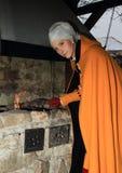 Κορίτσι στην ιστορική θέρμανση φορεμάτων στη σχάρα Στοκ Εικόνες