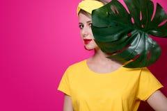 Κορίτσι στην κίτρινη μπλούζα κοντά στο φύλλο φοινικών στοκ φωτογραφίες με δικαίωμα ελεύθερης χρήσης