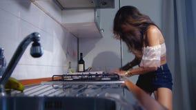Κορίτσι στην κουζίνα στις συγκινήσεις απόθεμα βίντεο