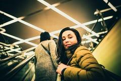 Κορίτσι στην κυλιόμενη σκάλα στο εμπορικό κέντρο Στοκ Φωτογραφίες