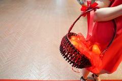 Κορίτσι στην κόκκινη εκμετάλλευση oragne στο καλάθι στοκ φωτογραφίες