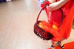Κορίτσι στην κόκκινη εκμετάλλευση oragne στο καλάθι στοκ εικόνα με δικαίωμα ελεύθερης χρήσης