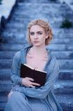 Κορίτσι στην μπλε εκλεκτής ποιότητας συνεδρίαση φορεμάτων με ένα βιβλίο στα σκαλοπάτια Στοκ φωτογραφία με δικαίωμα ελεύθερης χρήσης