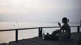 Κορίτσι στην παραλία με ένα smartphone σε ένα ταξίδι απόθεμα βίντεο