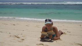 Κορίτσι στην παραλία που διαβάζει ένα βιβλίο απόθεμα βίντεο