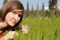 Κορίτσι στην πράσινη χλόη σε ένα μαλακό υπόβαθρο της πόλης Στοκ Φωτογραφίες