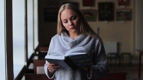 Κορίτσι στη βιβλιοθήκη που διαβάζει ένα βιβλίο φιλμ μικρού μήκους