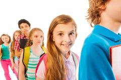 Κορίτσι στη γραμμή που χαμογελά μεταξύ άλλων σπουδαστών Στοκ Φωτογραφίες