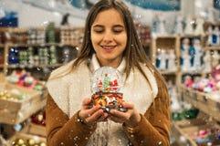 Κορίτσι στη θερμή σφαίρα γυαλιού εκμετάλλευσης παλτών με firtrees, το σπίτι και το τεχνητό χιόνι σε μια λεωφόρο στην έκθεση Χριστ στοκ εικόνες